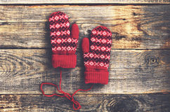 Red woolen mittens on rustic wooden background Stock Photos