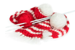 Red woolen scarf, knitting needles and balls of yarn Royalty Free Stock Image