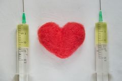 Red woolen toy heart lying between two syringes filled with a yellow medicine on the white bed hospital sheet. Heart treatment, cardiology, health concept stock image