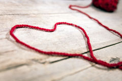 Red woollen ball and string on wooden background, symbol Heart Royalty Free Stock Images