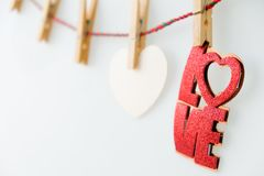 Red word LOVE on rope with clothespins, on a white. Background royalty free stock photos