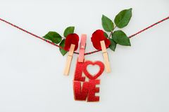 Red word LOVE and rose on rope with clothespins. On a white background stock image