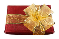 Red wrapped gift box with a big golden bow Royalty Free Stock Photography