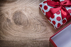 Red wrapped gift box with ribbon on wooden board celebrations co Royalty Free Stock Photos