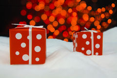 Red wrapped gift in front of Christmas tree Royalty Free Stock Photography