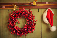 Red wreath with Santa hat hanging on rustic wall stock photography