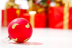 Red xmas ball. Present boxes in the background Royalty Free Stock Photos