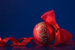 Red xmas ball on dark blue background. With space for text Royalty Free Stock Image