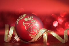 Red xmas ball with golden ribbon on red background. Red xmas ball with golden ribbon on red blurred background Stock Images