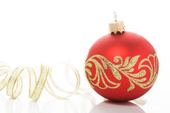 Red xmas ball and golden ribbon. On the white Royalty Free Stock Photo