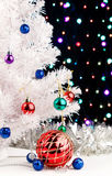 Red xmas ball near by decorated white fir-tree. Red christmas ball and blue balls garland near by white fir-tree on blurred lights background Royalty Free Stock Photo