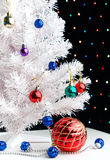Red xmas ball near by decorated white fir-tree. Red christmas ball and blue balls garland near by white fir-tree on blurred lights background Stock Photo