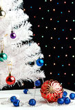 Red xmas ball near by decorated white fir-tree. Red christmas ball and blue balls garland near by white fir-tree on blurred lights background Royalty Free Stock Photos
