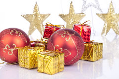 Red xmas balls and gifts. Red xmas balls and golden gifts on white Stock Photography