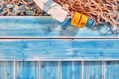 Red y boya de pesca en tablones de madera pintados azul Imagenes de archivo