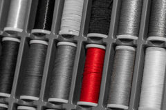 Red Yarn alone. Between grey ones stock photo