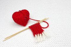 Red yarn ball like a heart and the beginning of red Santa scarf on the white crochet background. Romantic Valentines Day or Christ Stock Photo