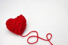 Red yarn ball like a heart on the white crochet background. Romantic Valentines Day concept. Red heart made of wool yarn with plac. Red yarn ball like a heart on Stock Photos
