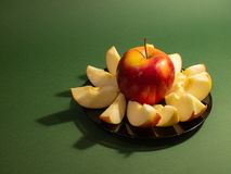 Red yellow apple and slice isolated on green background stock photo