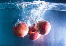 Red-yellow apples falling into clear water royalty free stock photo