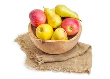 Red and yellow apples and pears in wooden fruit bowl. Red and yellow apples and European pears in vintage wooden fruit bowl on a sackcloth on a white background Stock Photos