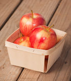 Red and yellow apples in a small woven wood basket Stock Images