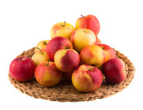 Red and yellow apples on a straw mat Stock Image