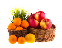 Red and yellow apples, tangerines and lemons in a wooden basket Royalty Free Stock Photo