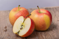 Red yellow apples on a wooden background Royalty Free Stock Image