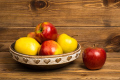 Red and yellow apples on the wooden plate on the rustic background. Red and yellow apples on the wooden plate on the brown rustic background Stock Image