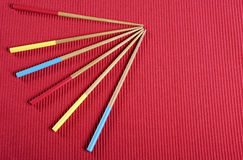 Red, yellow and aqua blue chopsticks on red mat table place setting. Royalty Free Stock Photos