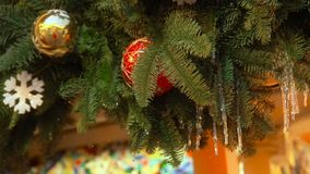 Red and yellow balls christmas tree garland with melting icicles and slowly falling snow decoration hanging on stret. Season fair. Christmas decorations stock footage
