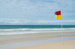 Red and yellow beach patrol flag on the Gold Coast. Royalty Free Stock Image