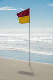 Red and yellow beach patrol flag on the Gold Coast. Royalty Free Stock Images