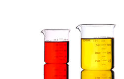 Red and Yellow Beakers. Two beakers containing red and yellow liquids, isolated on white Royalty Free Stock Photography