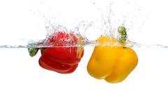 Red and yellow Bell Pepper splashing. Fresh yellow and red Bell Pepper splashing into water Royalty Free Stock Image