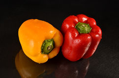 Red and Yellow bell peppers. Fresh bell peppers on a wet black background Royalty Free Stock Photography