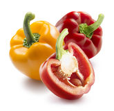 Red yellow bell peppers plus half  on white background Royalty Free Stock Photography