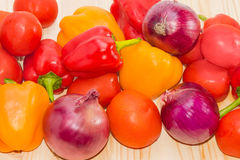 Red and yellow bell peppers, tomatoes and red onions closeup Stock Images