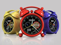 Red yellow blue alarm clocks. Red yellow blue exclusive mechanical alarm clocks with a tourbillon on a gray background with reflection Royalty Free Stock Photo