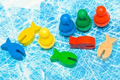 Red, yellow, blue, green fish and penguin wood chips figure in children play - Board game and kids leisure concept. Board game and kids leisure concept - red stock images