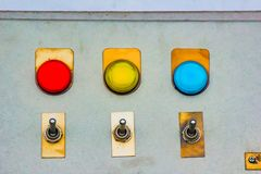 Red yellow blue lights indicator with changeover metal switch on a steel board panel.  royalty free stock photos