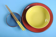 Red, yellow and blue theme table place setting with chopsticks. Royalty Free Stock Images