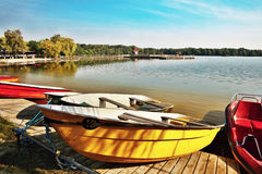 Red and yellow boats and pedal boats in shore of the Alum Lake Kamencove jezero in Chomutov in the region Ustecky kraj at the end. Of the summer season in Czech Stock Image