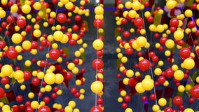 Multi-colored balls are stretched on ropes for decoration, swinging in the light. Red and yellow bright beads for decoration and decoration hang on horizontally stock video