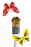 Red and yellow butterflies flying above paintbrush Royalty Free Stock Image