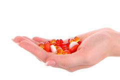 Red and yellow  capsules of vitamins on the hand Stock Photography