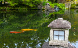 Red and yellow carp fish in a Zen pond in Japan with lantern Stock Photography