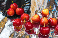 Red and yellow cherries in the black dish and foil background Stock Image