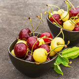 Red and yellow cherries in dark ceramic bowls on a dark background. Top view Royalty Free Stock Image